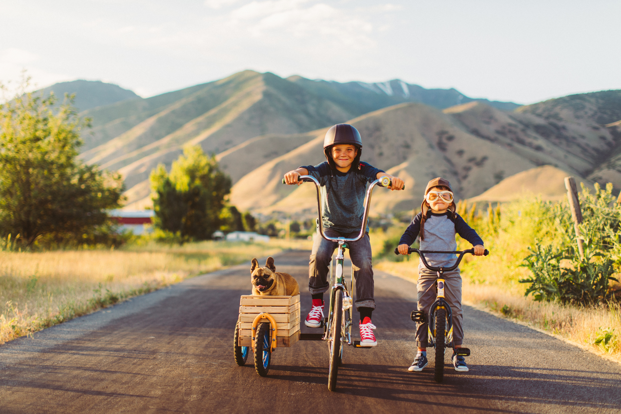 Two young boys with vintage clothing and motorcycle helmets rides their bicycles with a pet and best friend French Bulldog riding along in a side car in Utah, USA. Sometimes a road trip journey with your best friends and some fresh air in your face is the best medicine for the soul.