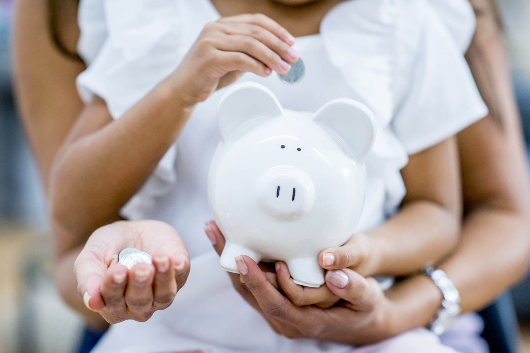 A mother and daughter are holding up a piggy bank. The daughter is putting coins into the bank.