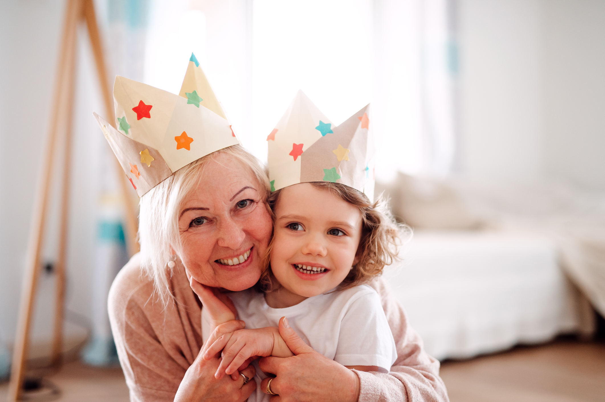 A portrait of small girl and grandmother with paper crown hugging at home.