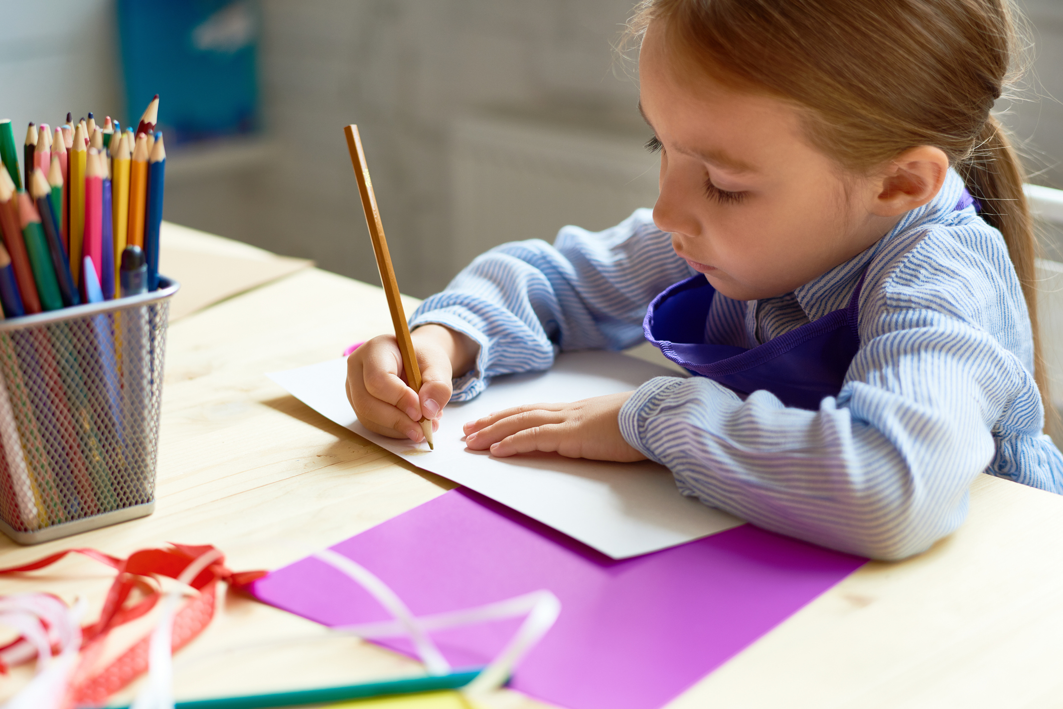 Portrait of cute little girl drawing picture at desk in art class, copy space