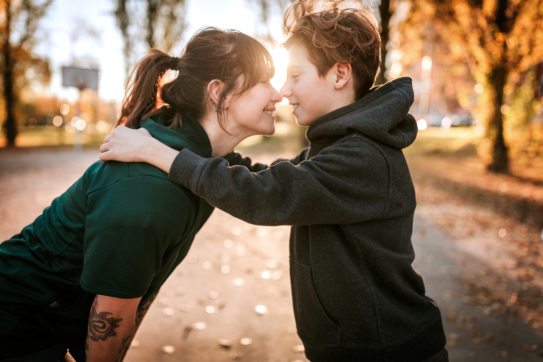 Young woman kissing and embracing her son outdoor, standing face to face on sunny day